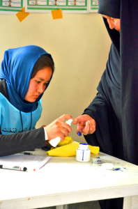 A woman has her finger marked with ink to confirm she has voted. (Photo: Jawad Kia)